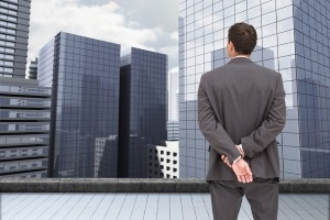 Composite image of businessman standing with hands behind back on the roof of building watching the city.jpeg